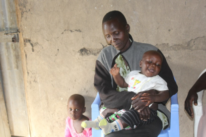 A Kenyan woman sitting down, holding a smiling baby. Another one of her young children is standing next to her.